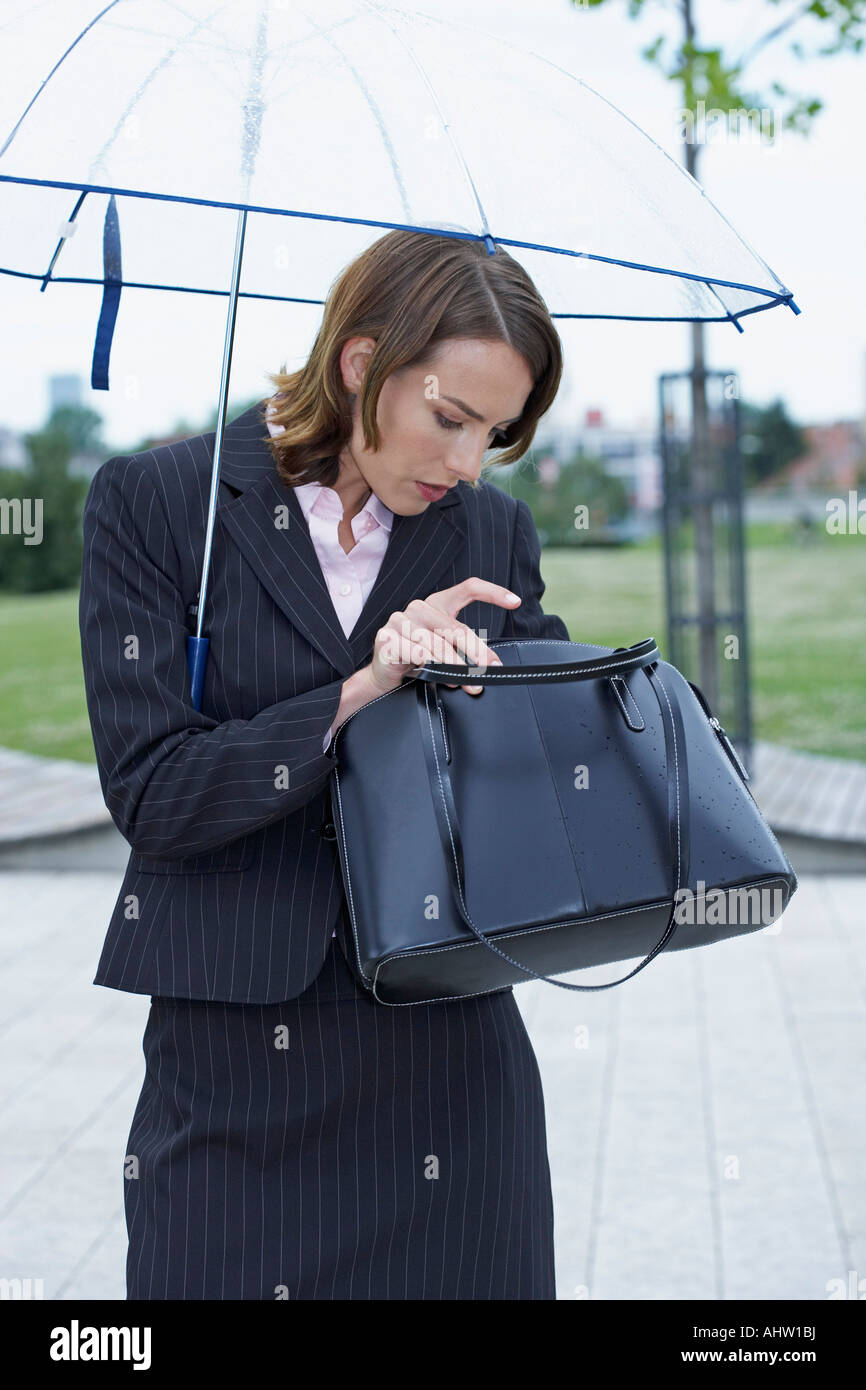 Businesswoman with umbrella fishing something out of handbag. - Stock Image