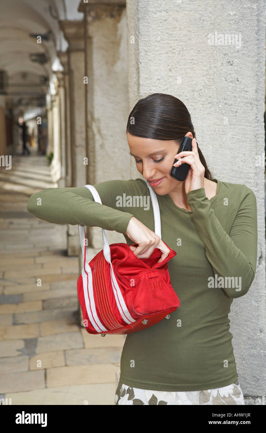 Young woman leaned at wall of ambulatories on the mobile fishing something out of her handbag smiling. - Stock Image