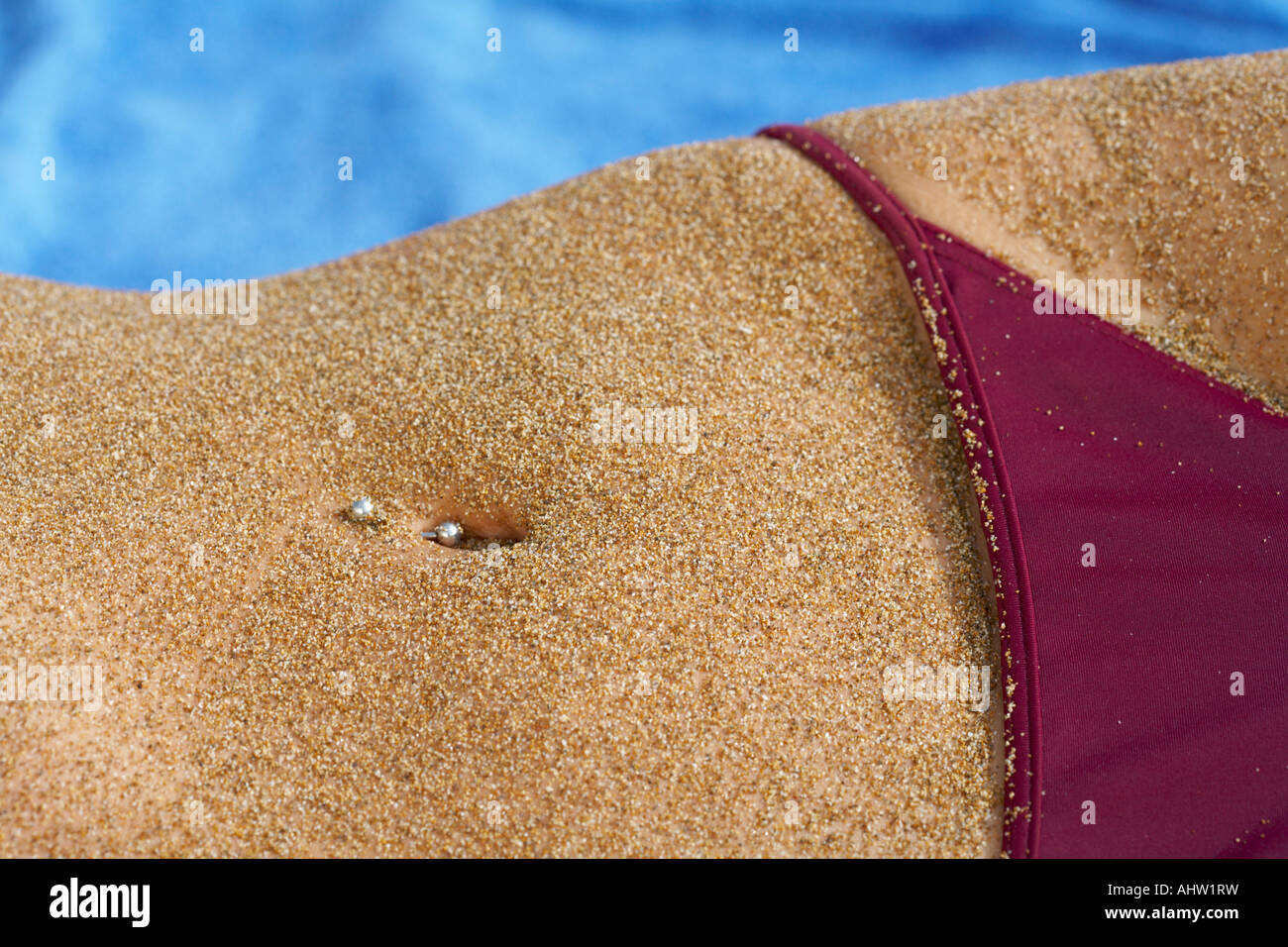 Close up of sandy belly piercing in belly button bikini bottom in section. - Stock Image