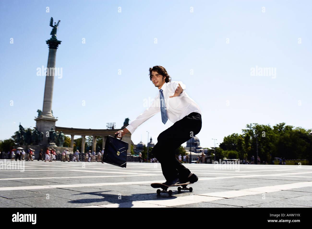 Businessman on skateboard in Hero Square. - Stock Image