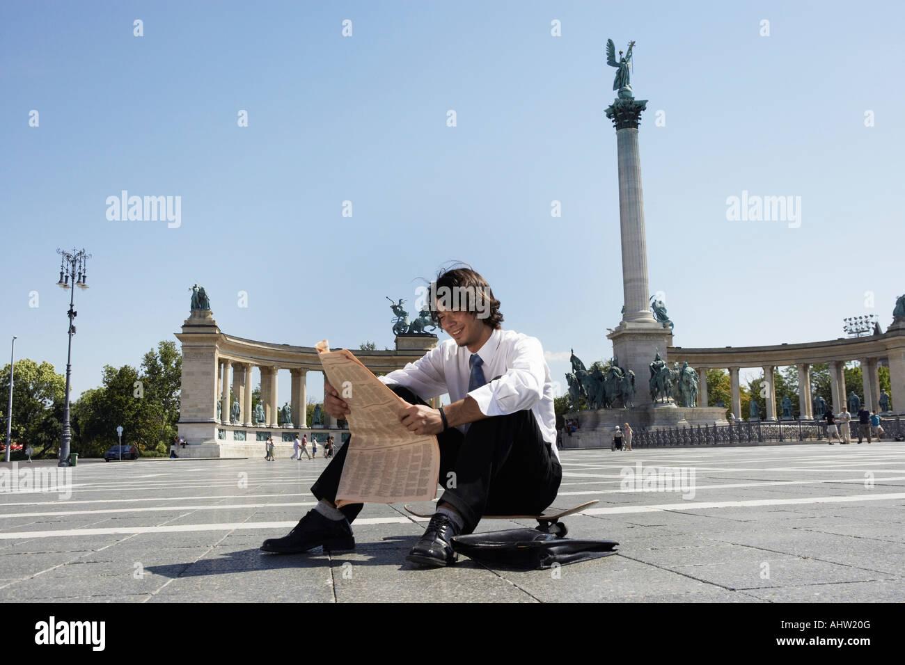 Businessman reading newspaper in Hero Square. - Stock Image