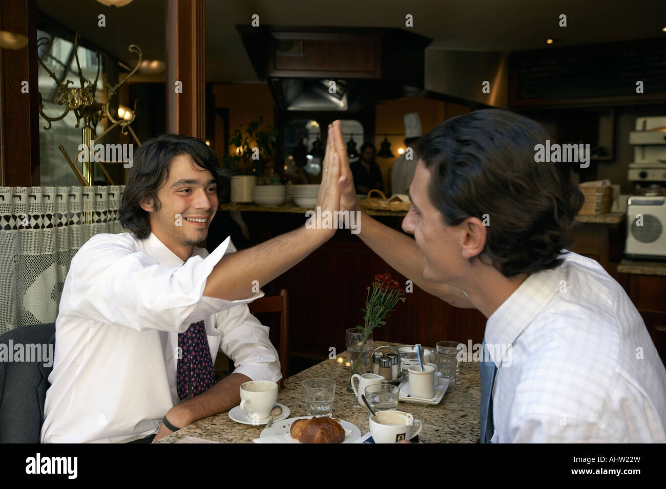 Businessmen giving a high five to each other. - Stock Image