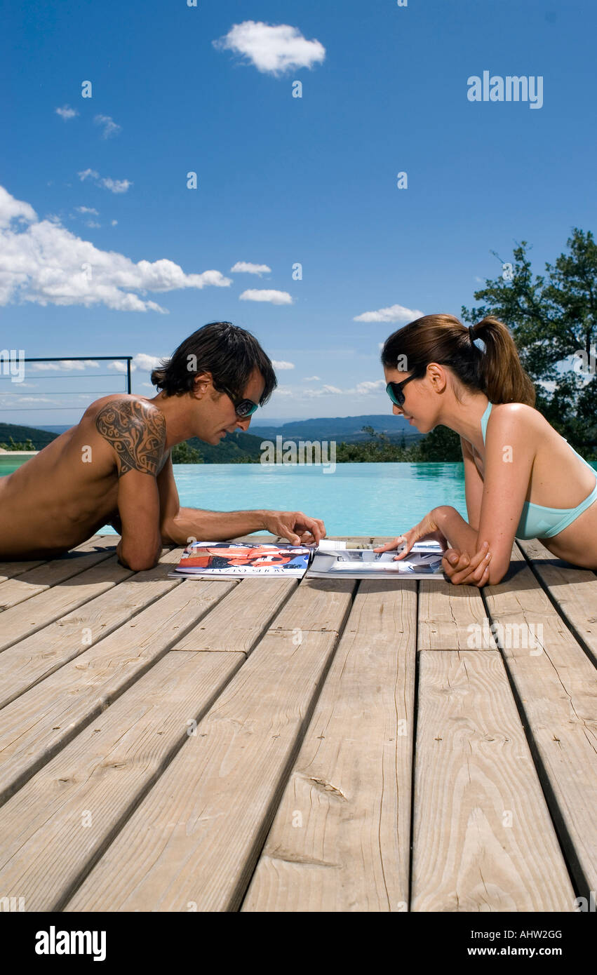 Couple sunbathing by a swimming pool with magazines Stock ...