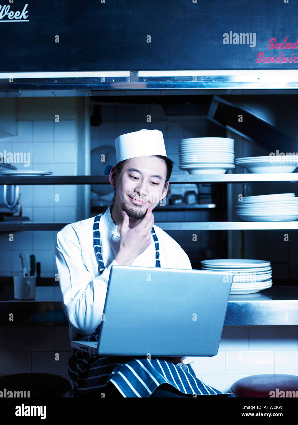 Chef looking at laptop in restaurant kitchen Stock Photo: 14548812 ...