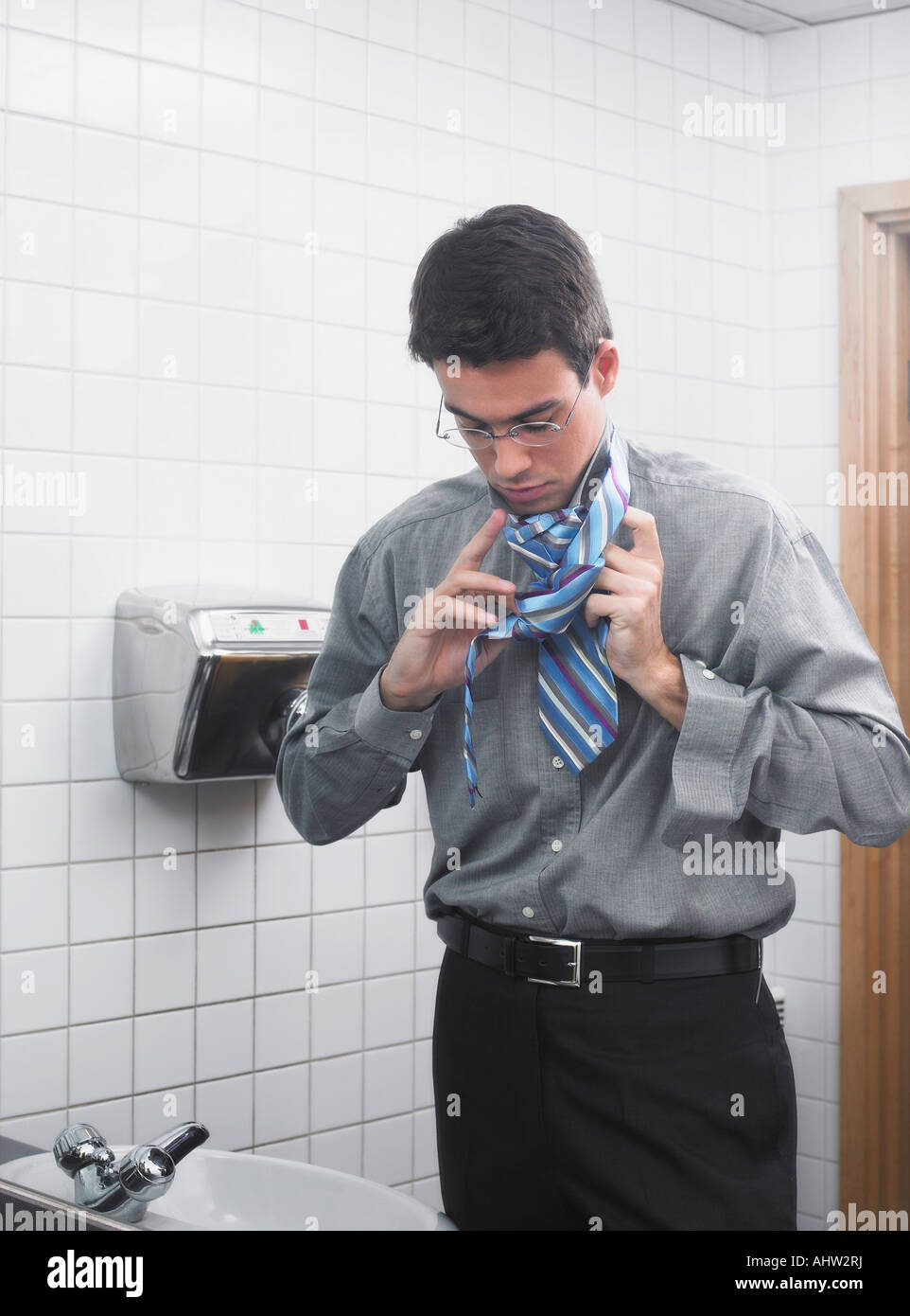 Man reflected in office washroom mirror doing up his tie Stock Photo