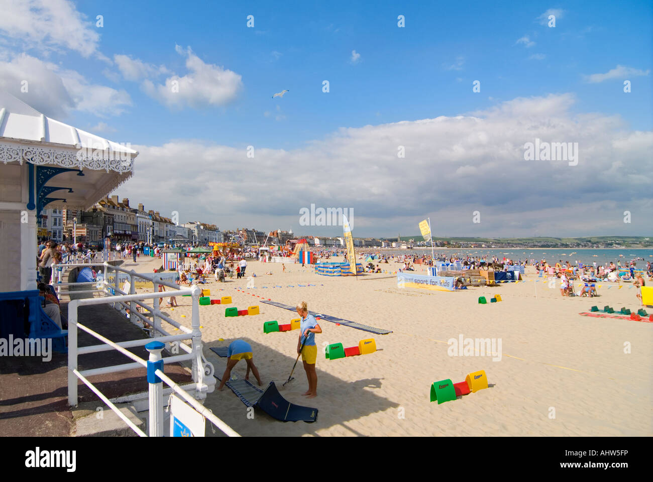 Horizontal wide angle of a typical English beach scene with lots of tourists on the sand at Weymouth Bay. - Stock Image
