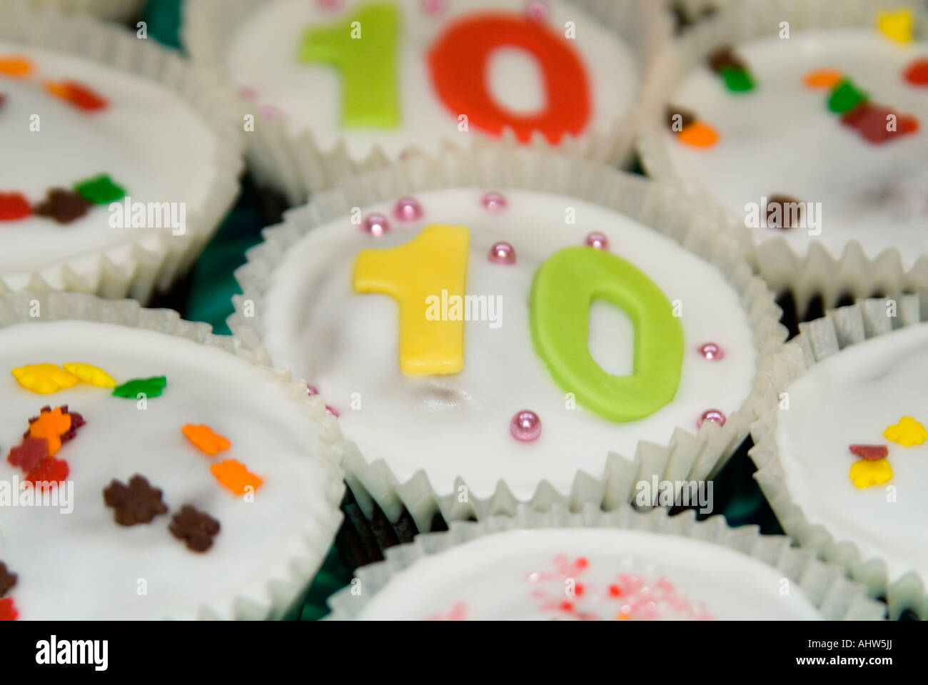 Horizontal close up of several homemade fairy cakes, aka cup cakes, decorated with icing and sugared sprinkles. - Stock Image