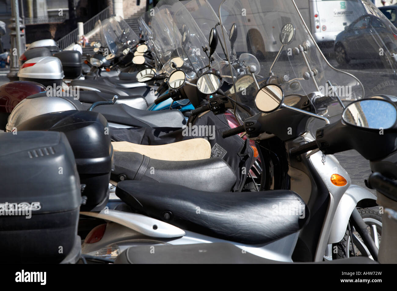 Row of seats and windshields of scooters parked on a street in Rome Lazio Italy - Stock Image