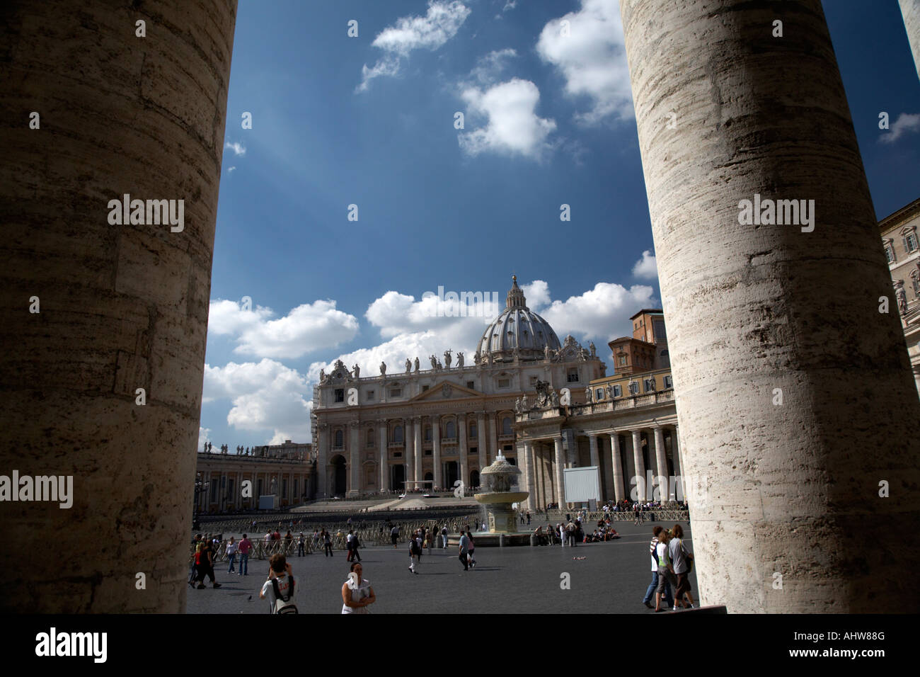 looking out through columns across the square to St Peters Basilica Vatican City Rome Lazio Italy - Stock Image