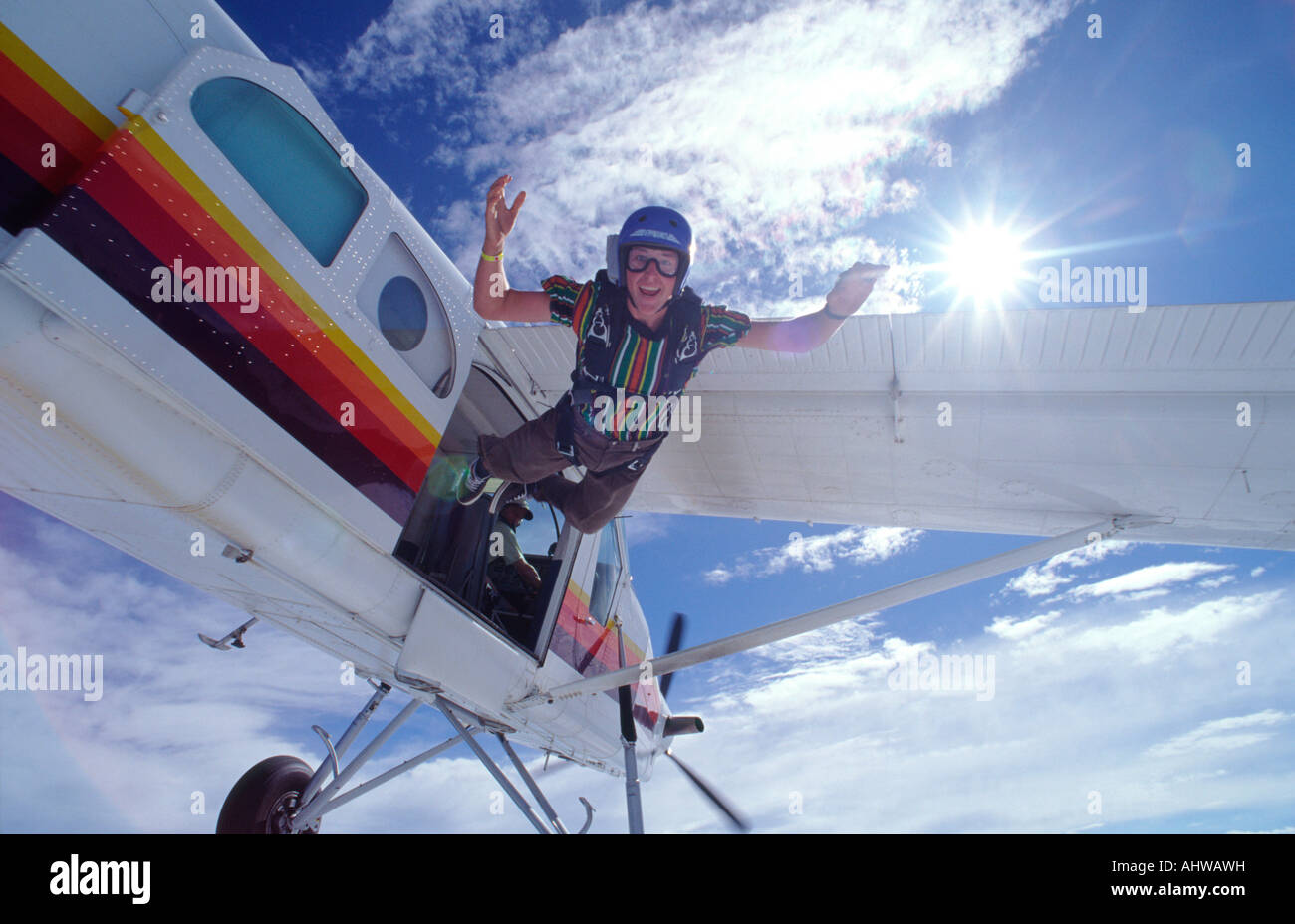 Skydiver in streetwear jumping from a Pilatus Porter Aircraft with sun in Background - Stock Image