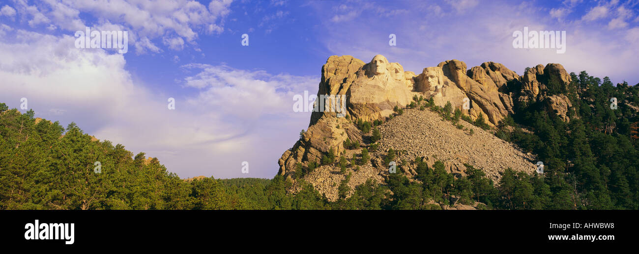 This is Mount Rushmore National Monument set into the mountain showing its natural surroundings against a blue sky Stock Photo