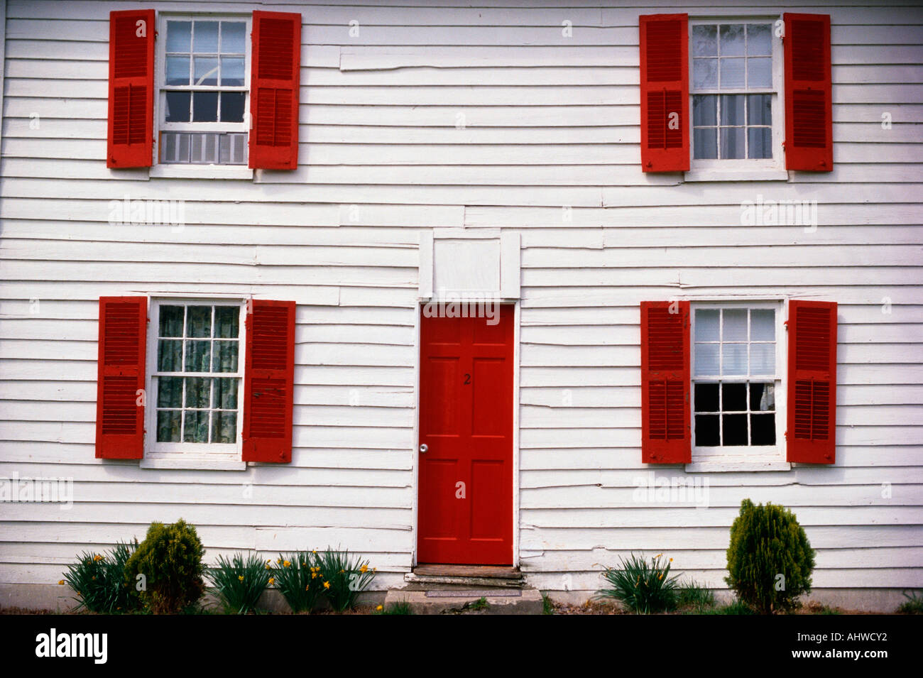 This Is A Close Up Of A White House With Red Shutters The Front Door