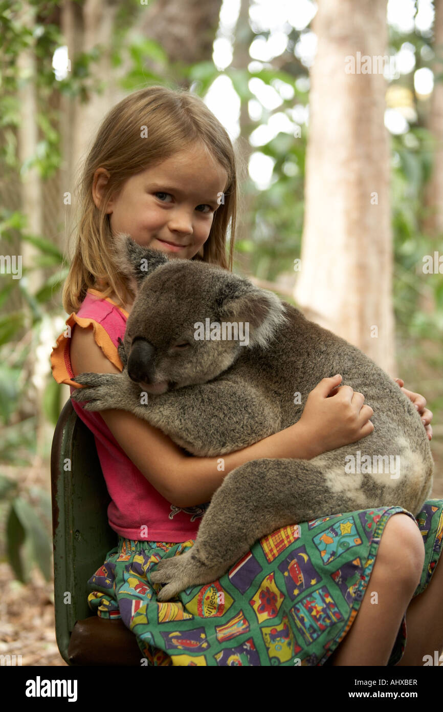 Young girl child holding a Koala bear in Lone Pine Koala Sanctuary wildlife reserve zoo Brisbane Queensland QLD - Stock Image