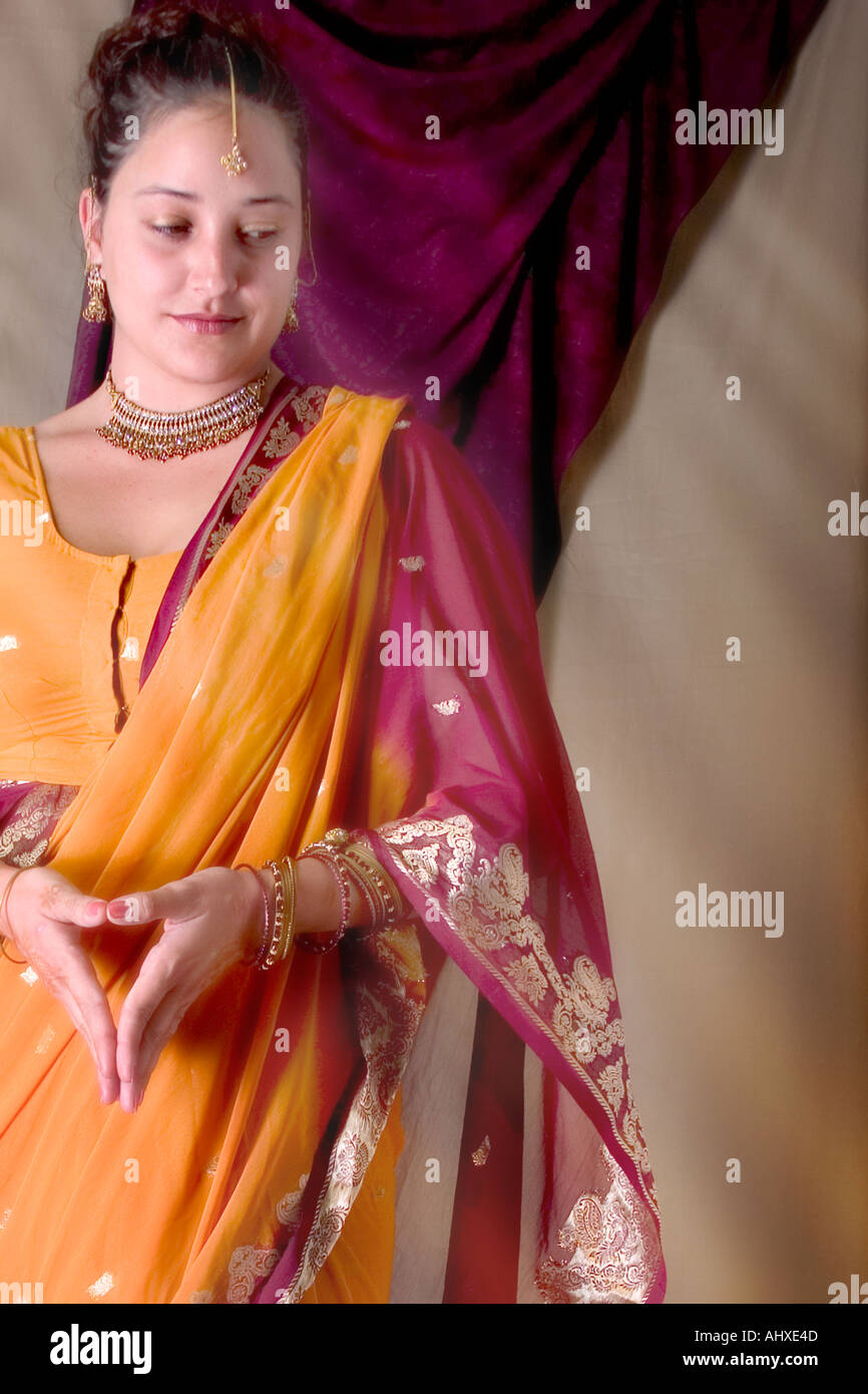 Mexican American female wearing a sari attending a cross cultural hindu american wedding ceremony - Stock Image