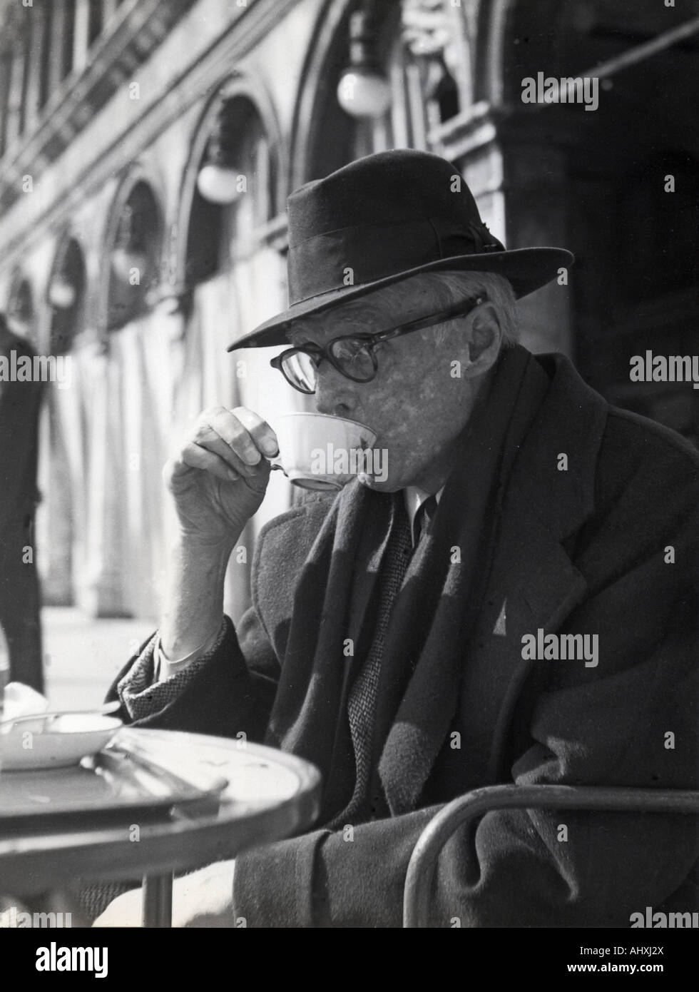 SINCLAIR LEWIS  US novelist sips a coffee in St Marks Square, Venice, during a visit to Italy in 1950 the year before - Stock Image