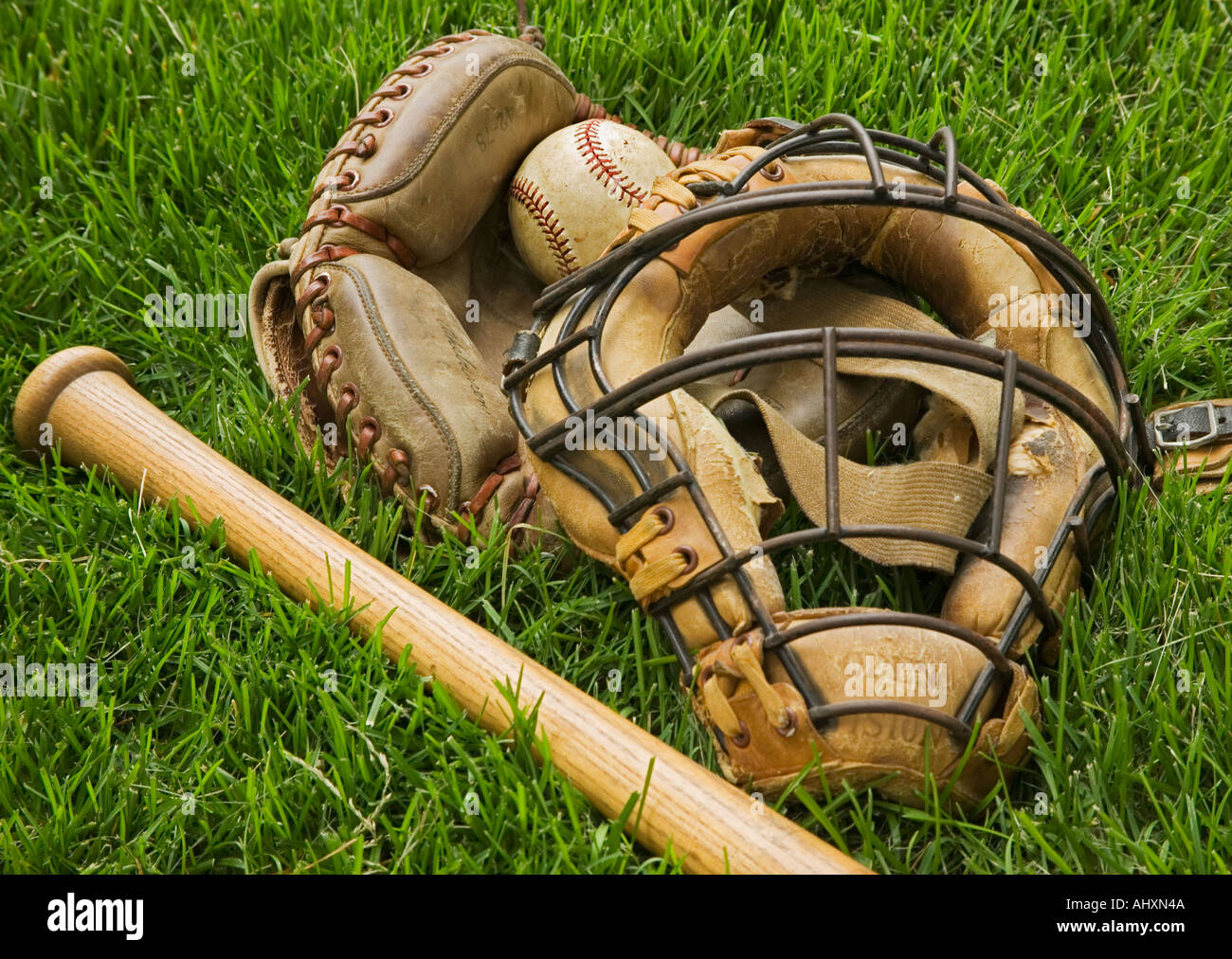 Old fashioned baseball equipment in grass - Stock Image