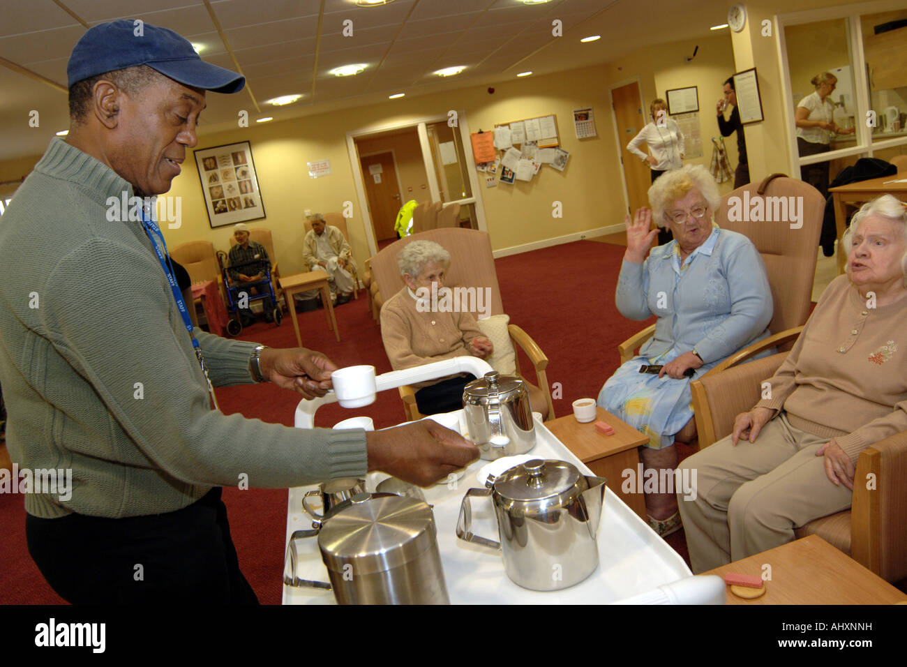 A Care Assistant serves tea to elderly people in a multi