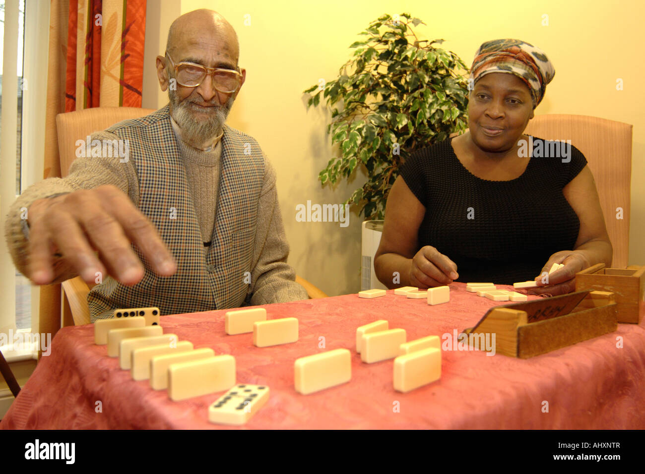 An elderly sikh man plays dominoes with a Care Assistant in