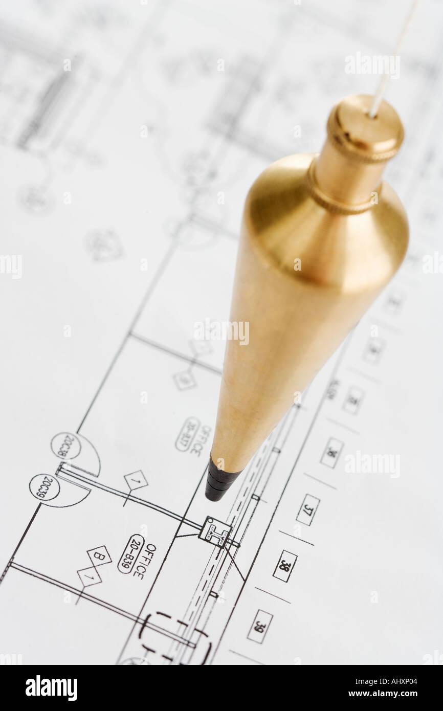 Plumb bob above blueprints - Stock Image