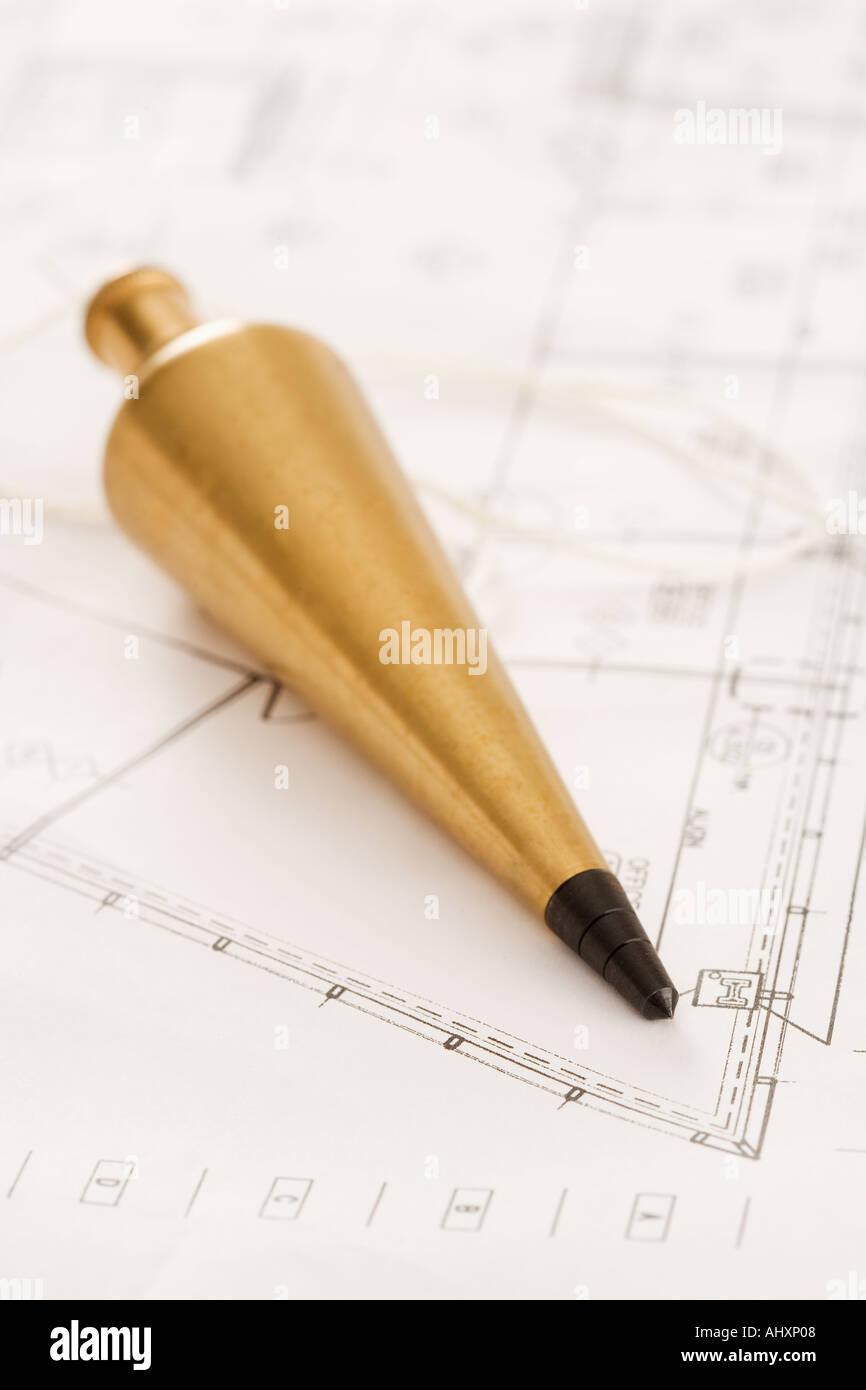 Plumb bob with blueprints - Stock Image