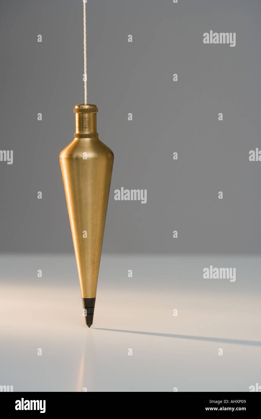 Plumb bob suspended from plumb line Stock Photo