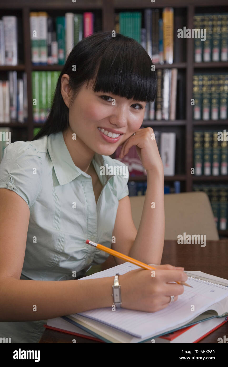 African female college student studying in library - Stock Image