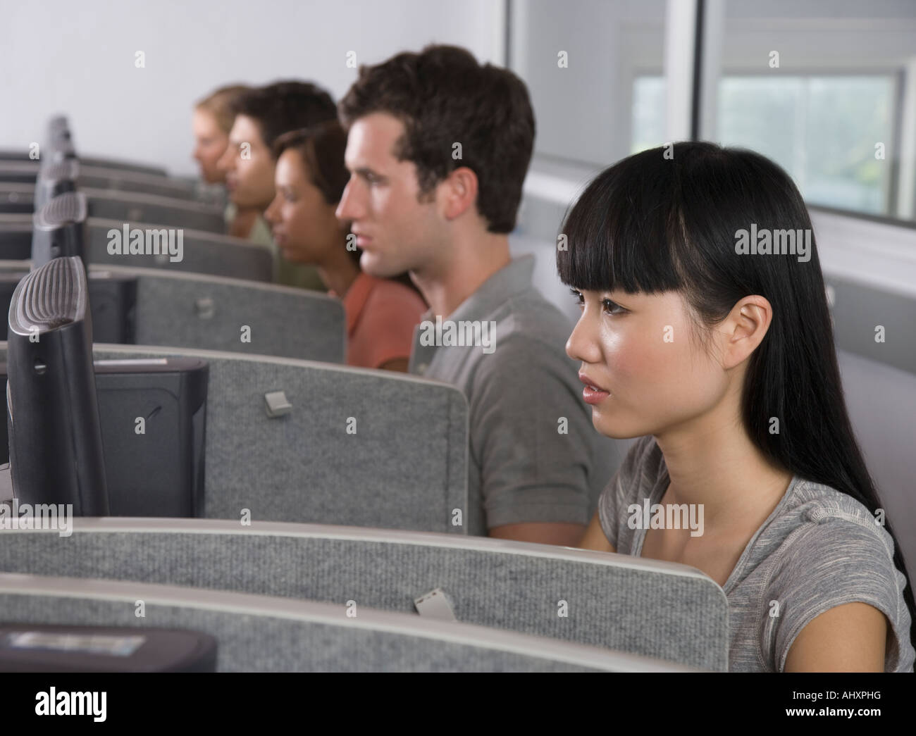 College students wearing headsets in computer lab - Stock Image