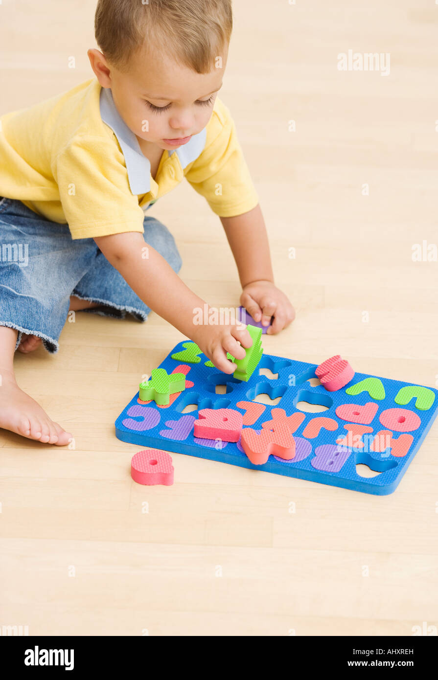 Baby playing with foam letters - Stock Image