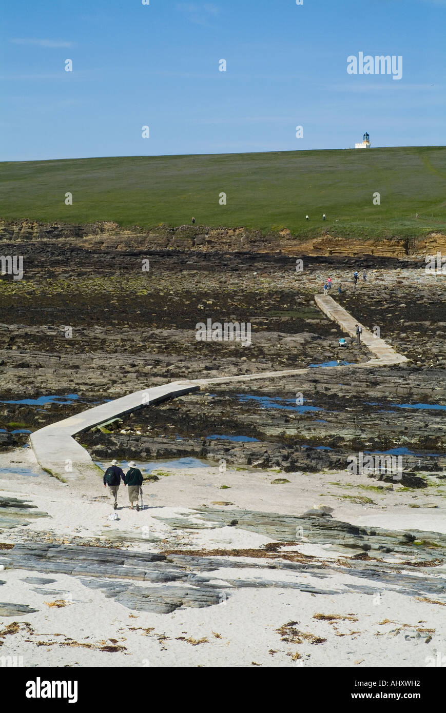 dh Brough of Birsay BIRSAY ORKNEY Couple walking over causeway to Birsay lighthouse island Stock Photo