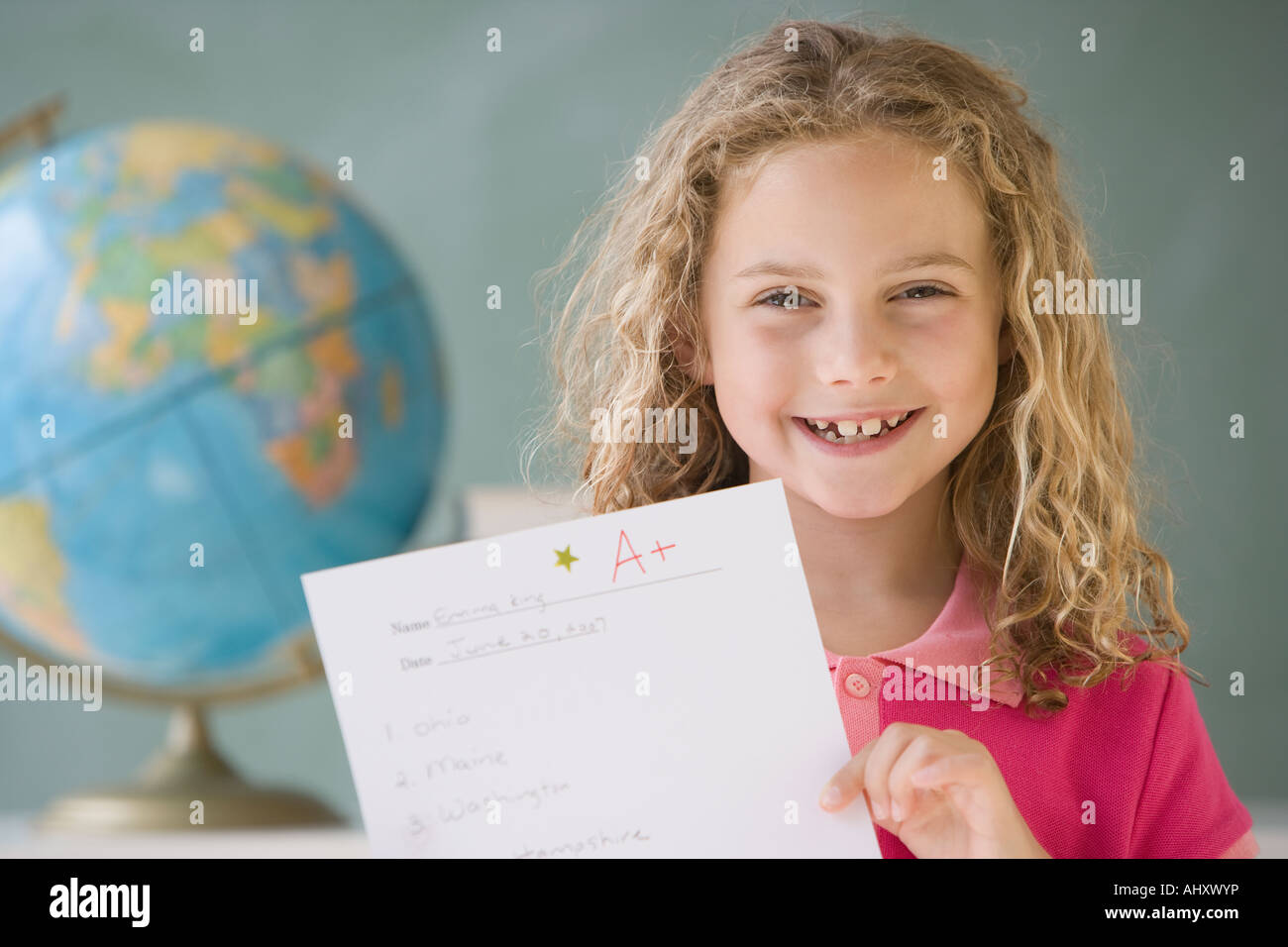 Girl holding up A plus paper in classroom - Stock Image