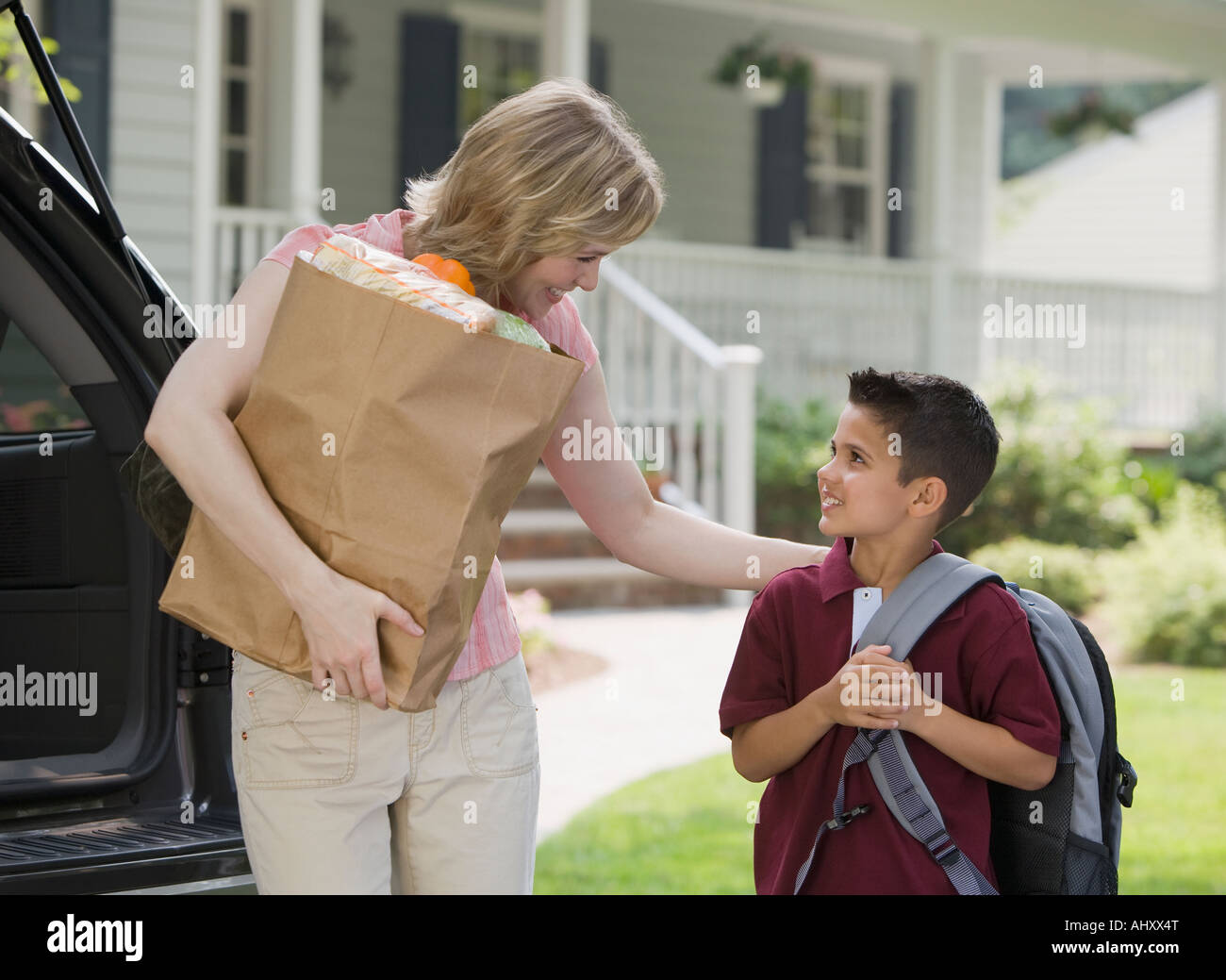Mother holding groceries and smiling at son - Stock Image