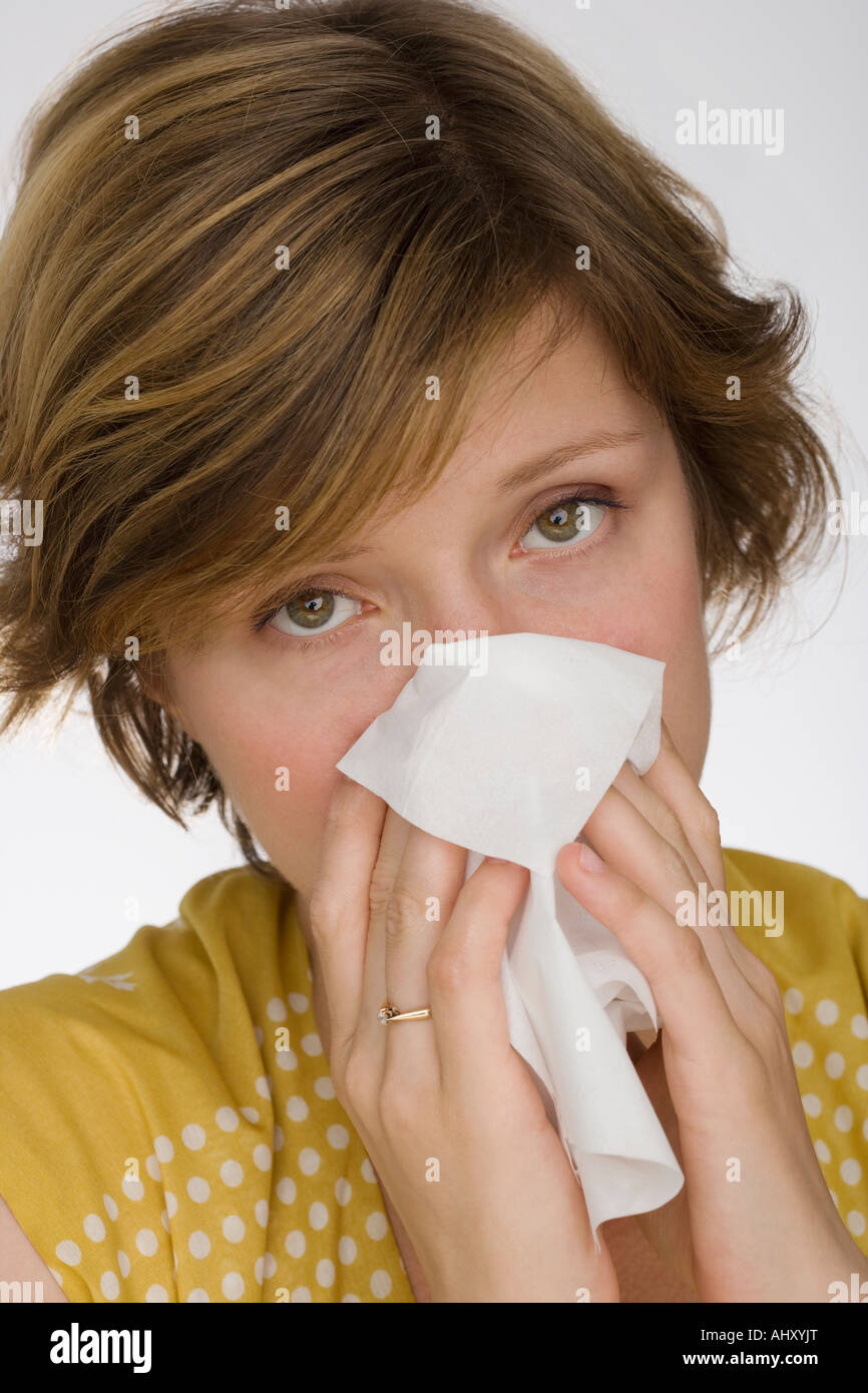 Close up of woman blowing nose - Stock Image