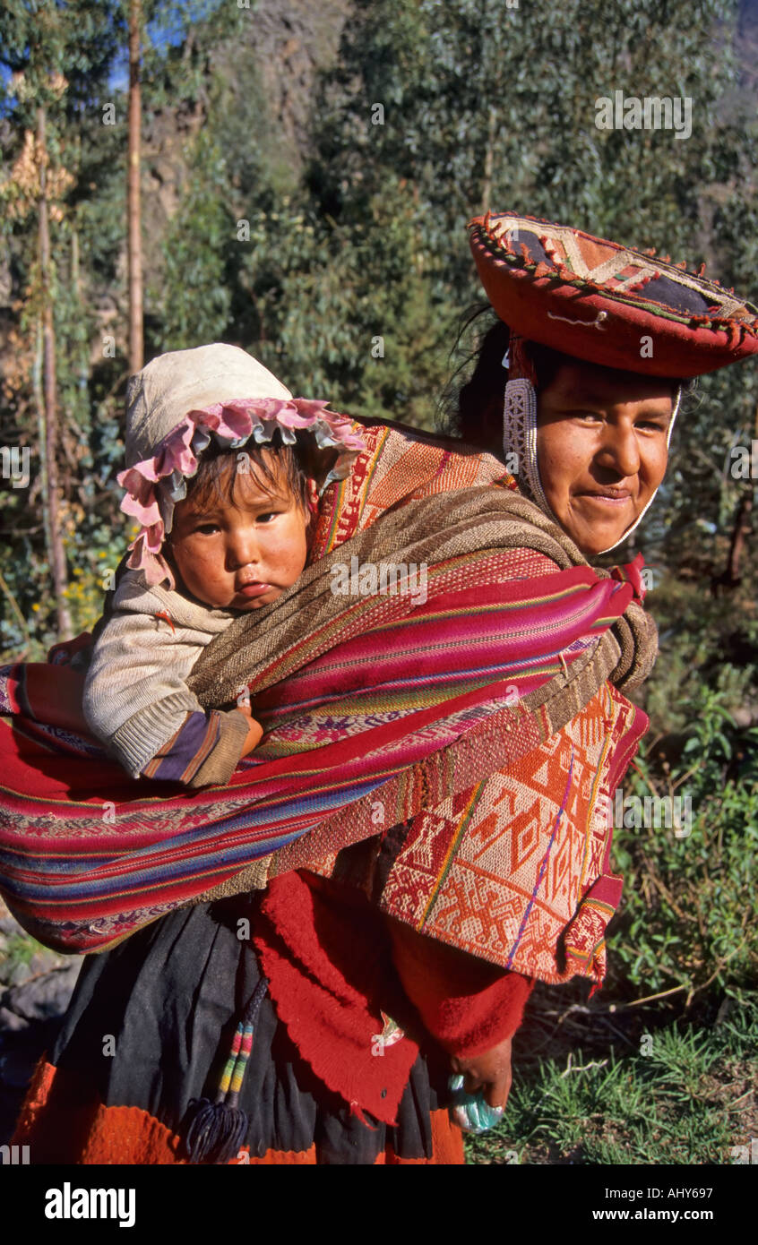 Quechua Indian woman carrying her child in a manta, Ollantaytambo, Peru - Stock Image