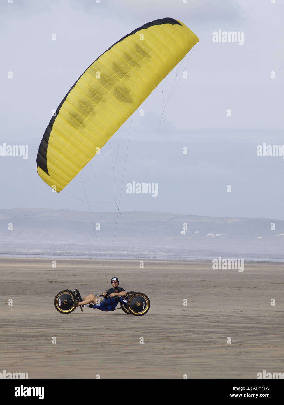 Parakarter directing his yellow kite, windy day on a sandy beach, upright Stock Photo