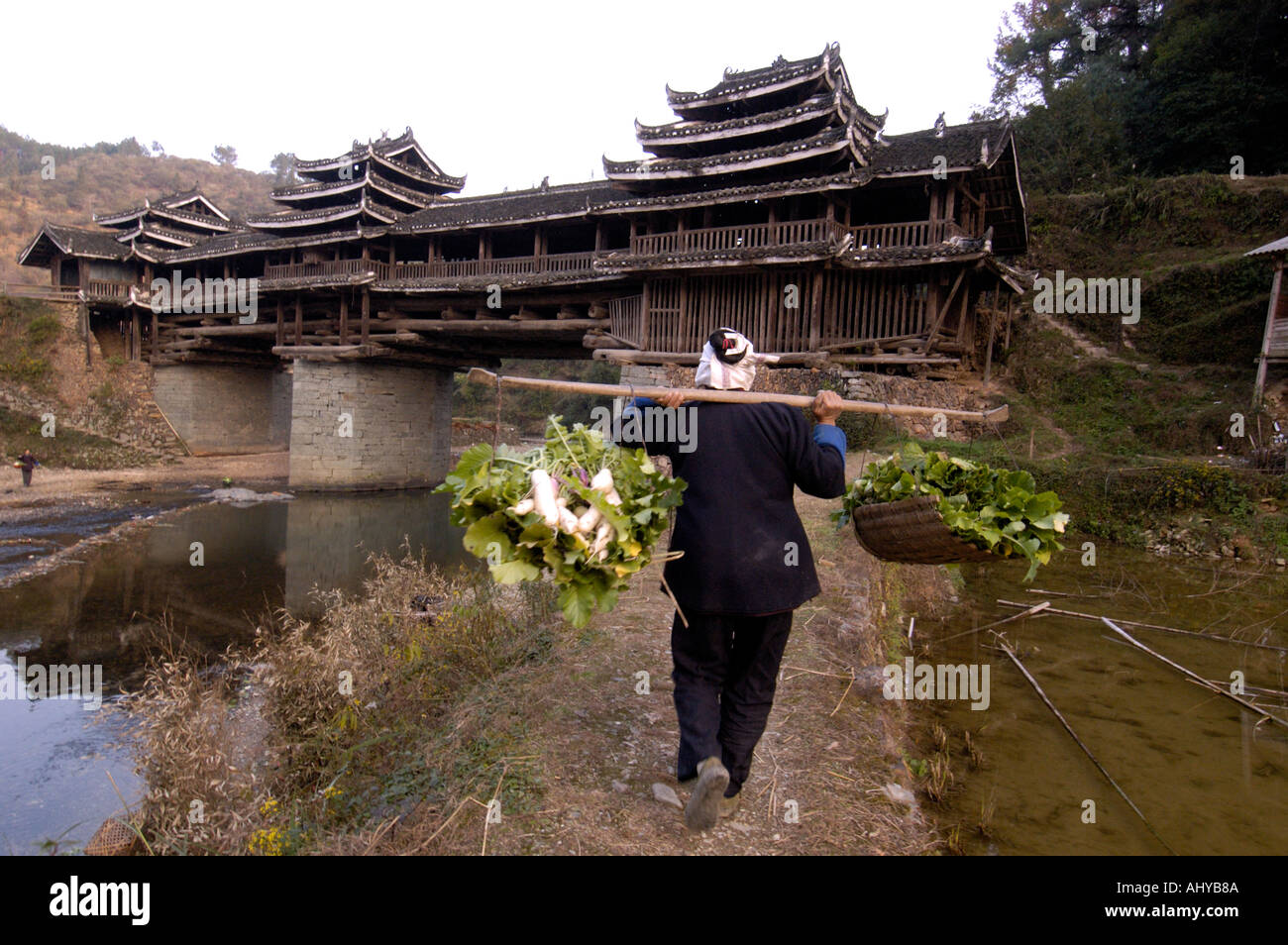 A Dong minority woman carries vegetables towards a wind and rain bridge in Sanjiang Guangxi Province in China 2005 Stock Photo