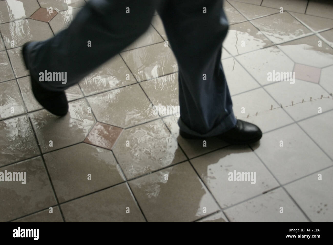 a pair of feet walking on slippery floor wet from rain Wearing blue jeans and black shoes Slight motion blur - Stock Image