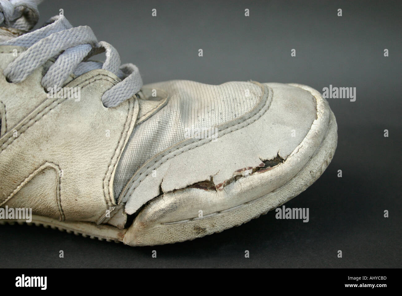 side view of dirty worn old sneakers or running shoes Concept comfort well used durability - Stock Image