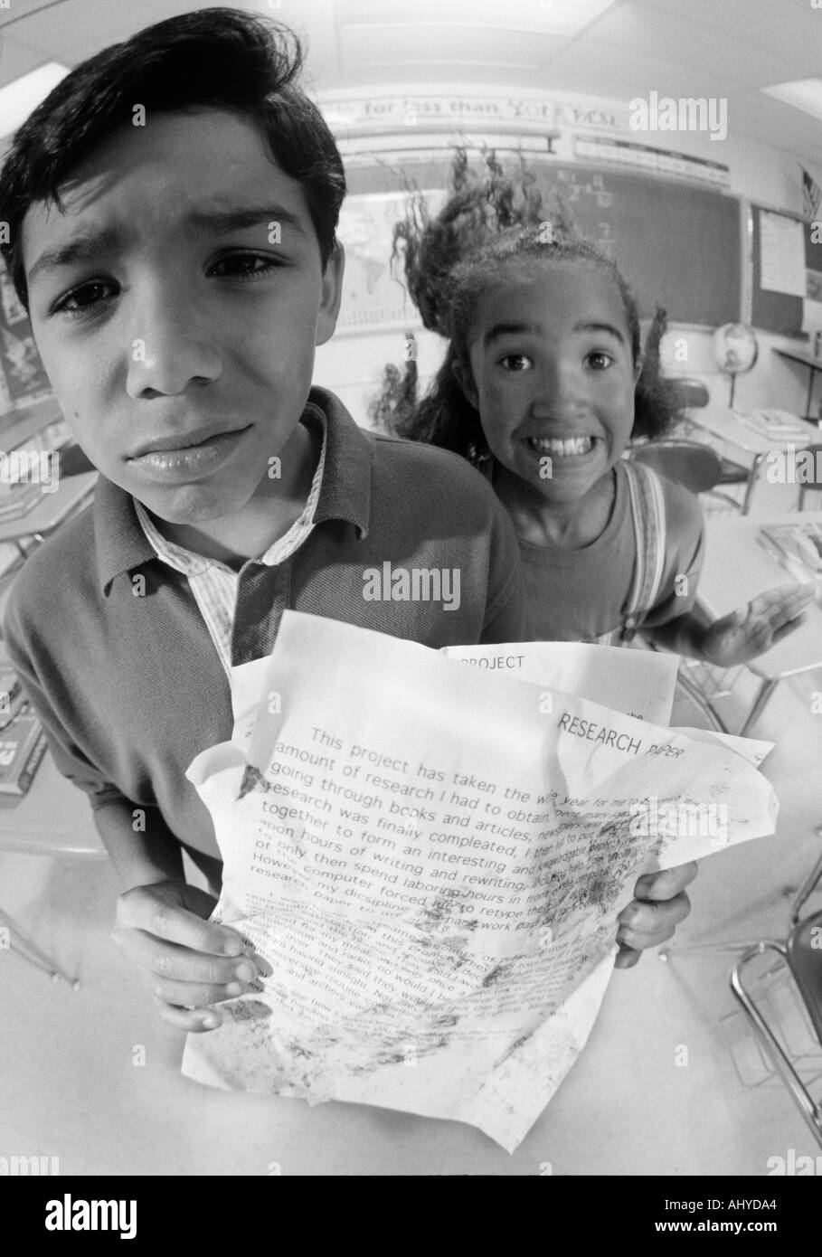 Two Latino middle school students with messy homework papers Using the excuse 'the dog ate my homework' - Stock Image