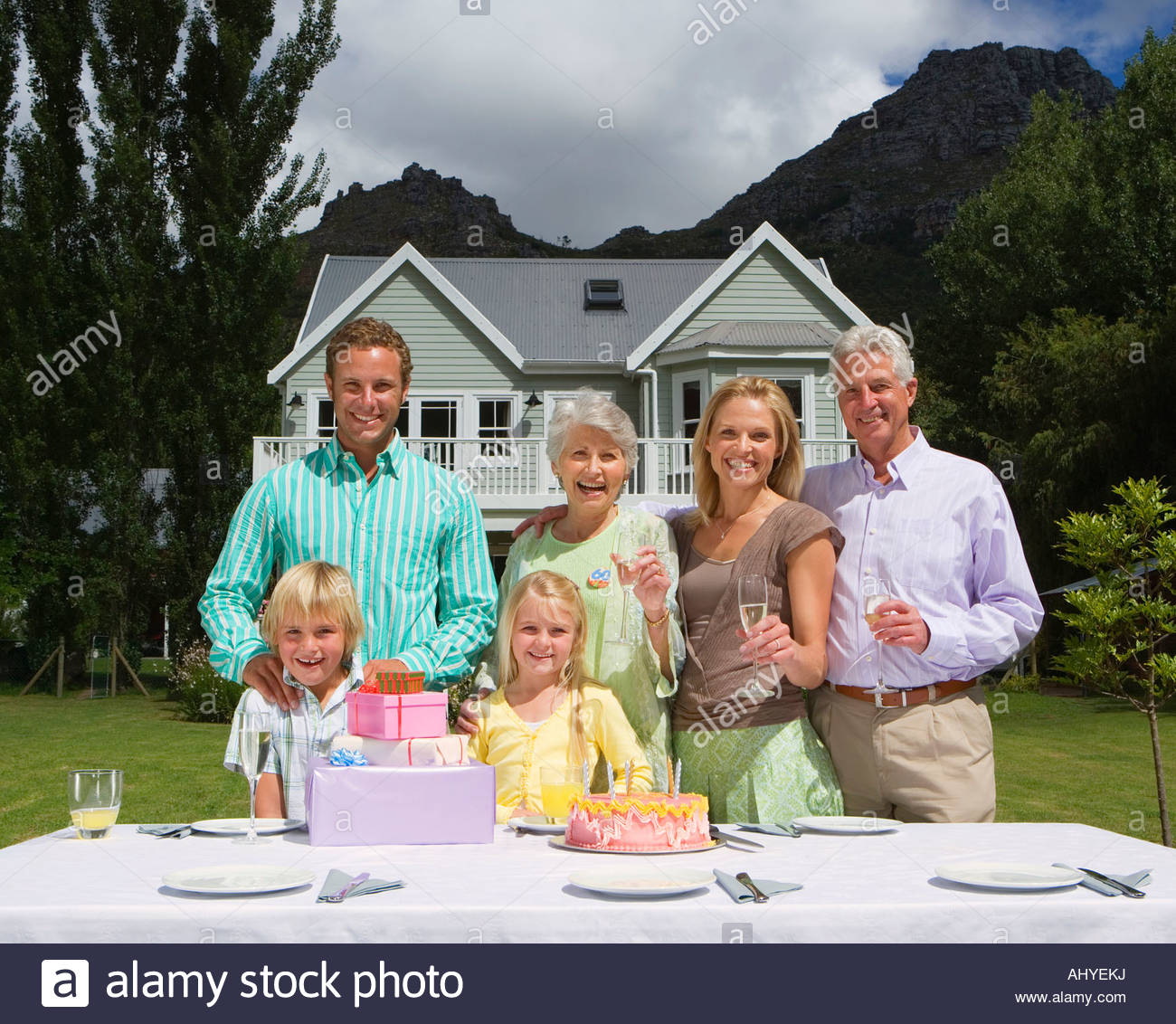 Three generation family celebrating birthday in summer garden in front of house smiling portrait - Stock Image