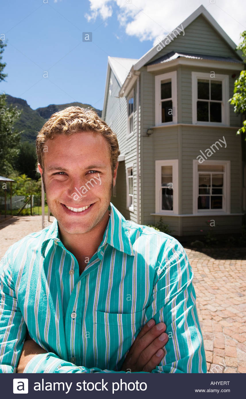 Man standing in driveway in front of detached house arms folded smiling portrait - Stock Image