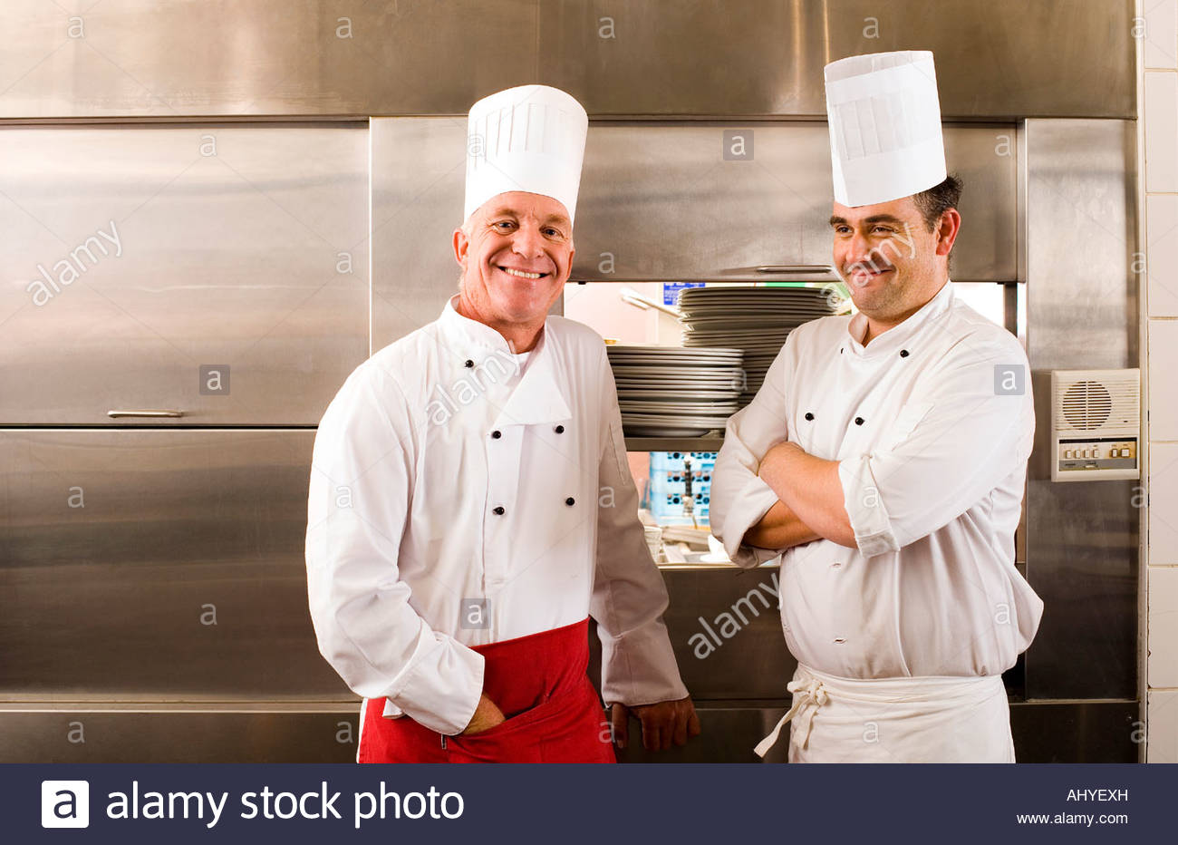 Two male chefs standing in commercial kitchen smiling portrait Stock Photo