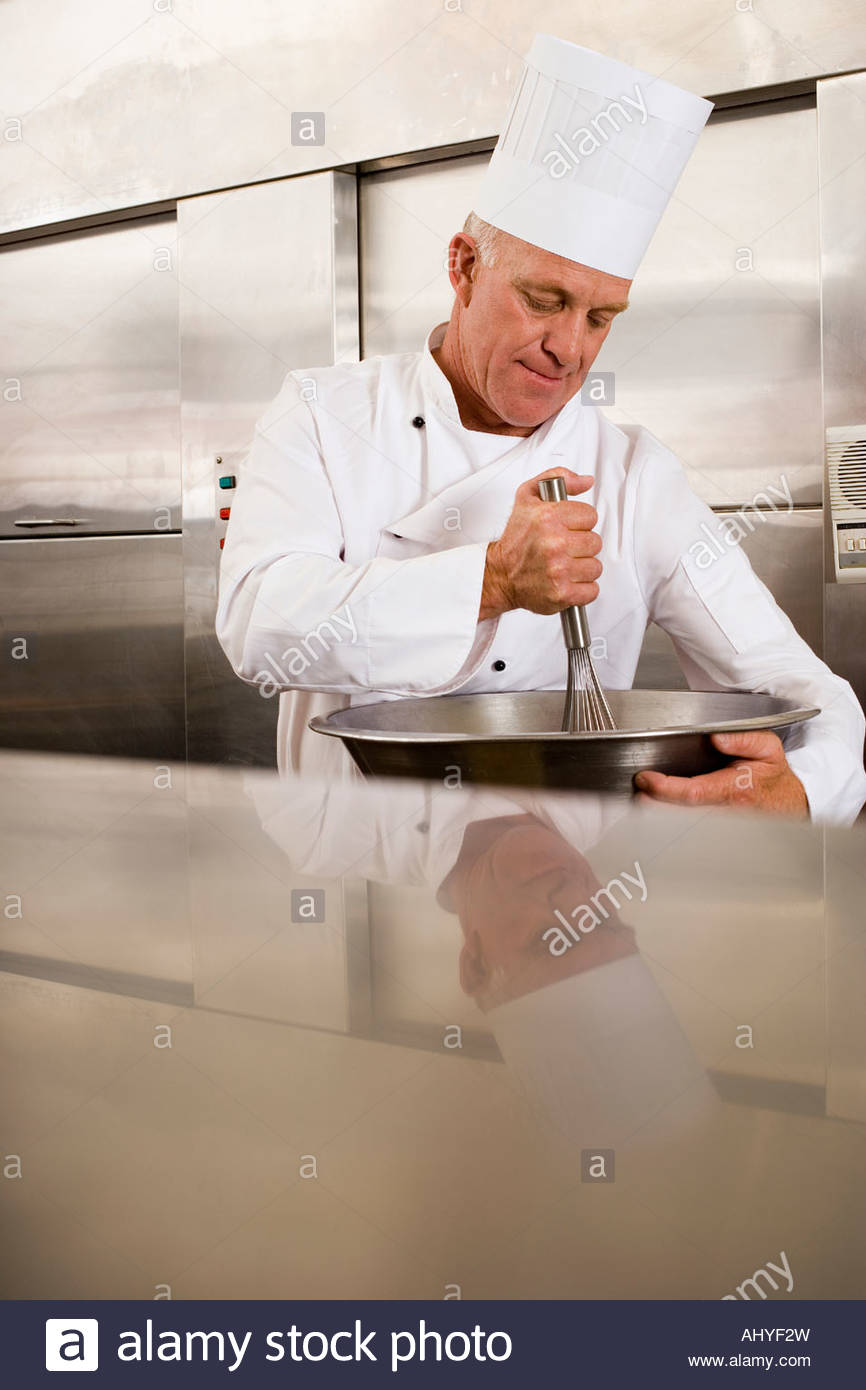 Mature male chef whisking ingredients in large bowl in commercial kitchen - Stock Image
