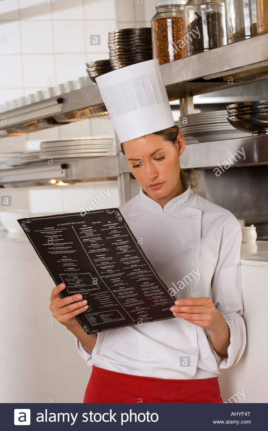 Female chef standing in commercial kitchen, looking at menu - Stock Image