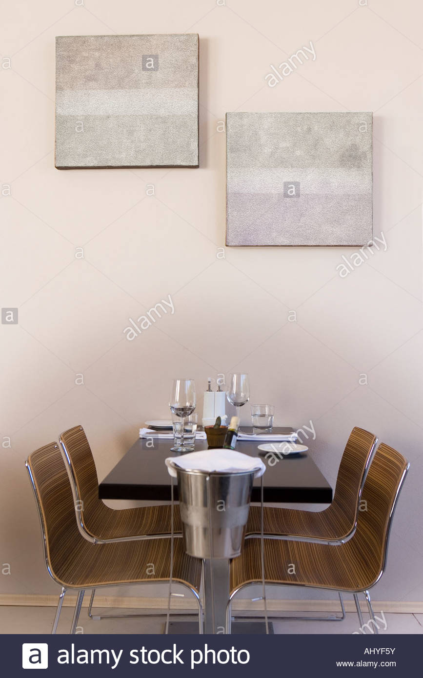 Ice bucket beside place settings on restaurant table, side view - Stock Image