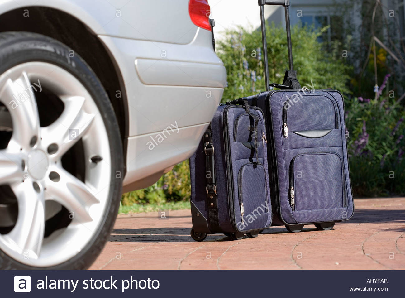 Two suitcases on wheels beside parked car on driveway surface level - Stock Image