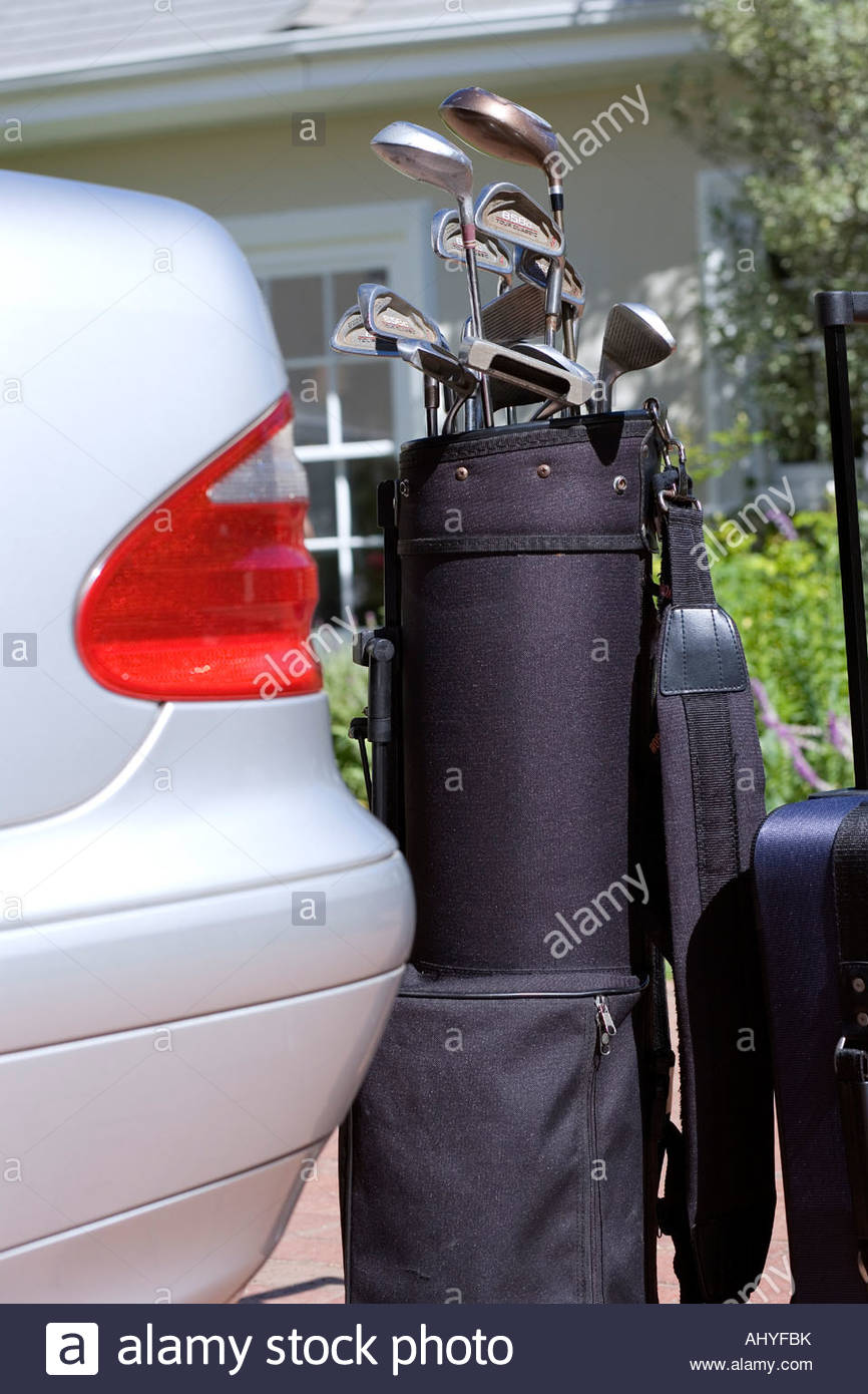 Set of golf clubs beside parked car on driveway, close-up - Stock Image
