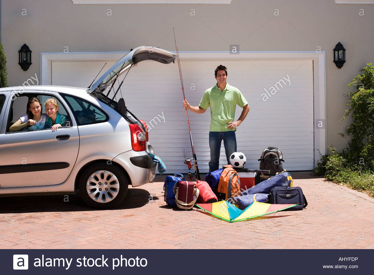 Father Loading Camping Equipment Into Car Boot On Driveway Holding Fishing Rod Children Sitting In Parked Smiling