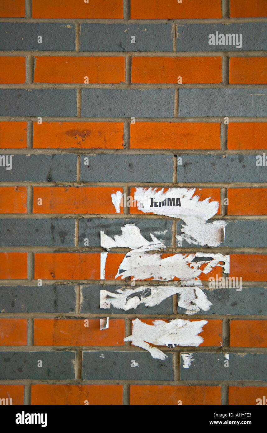 Partly removed post on two tone brick wall adjacent to the road running underneath the Eagle Centre car park in Derby, UK - Stock Image