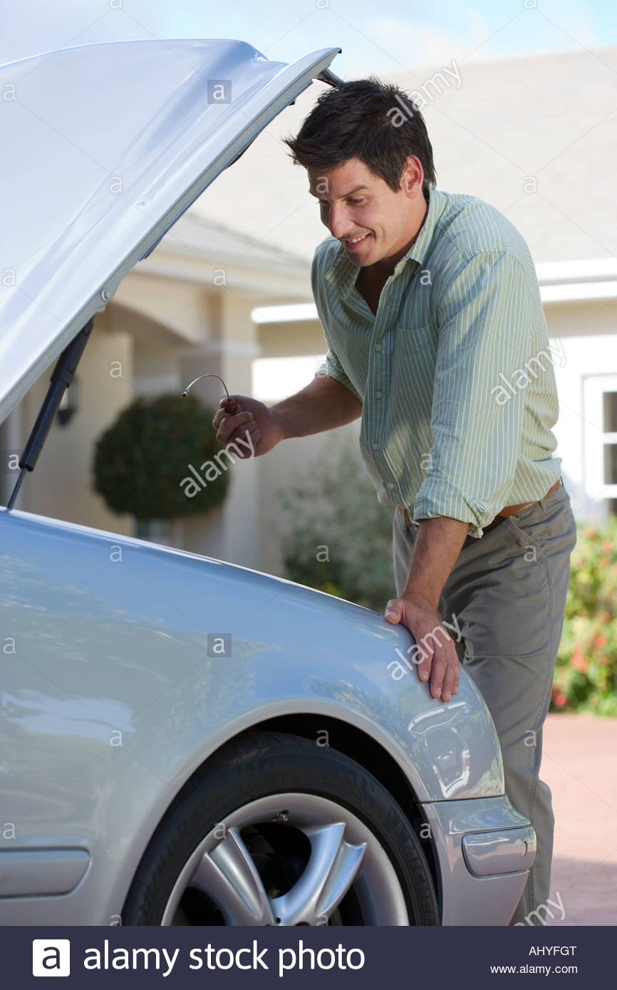 Man standing beside parked convertible car on driveway looking at engine smiling side view - Stock Image