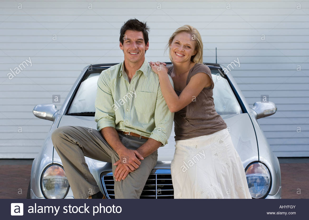 Couple leaning on bonnet of parked convertible car on driveway smiling front view portrait - Stock Image